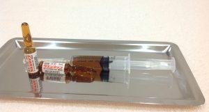 プラセンタ製剤である(株)日本生物のラエンネックのアンプルと注射器の画像です。アンプルは茶褐色で白地のラベルにに赤でラエンネックと書かれてます。注射器は5ccでラエンネック2アンプル4ccの褐色の薬剤で満たされてます。