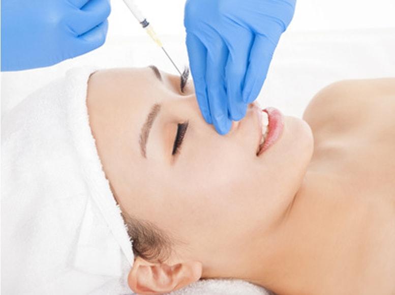 鼻にヒアルロン酸を注入する右側からみた女性のバストアップ画像です。施術者は手のみ写っており青い手袋をしています。女性の頭側から右手で注射器をもって注射しようとしているところです。