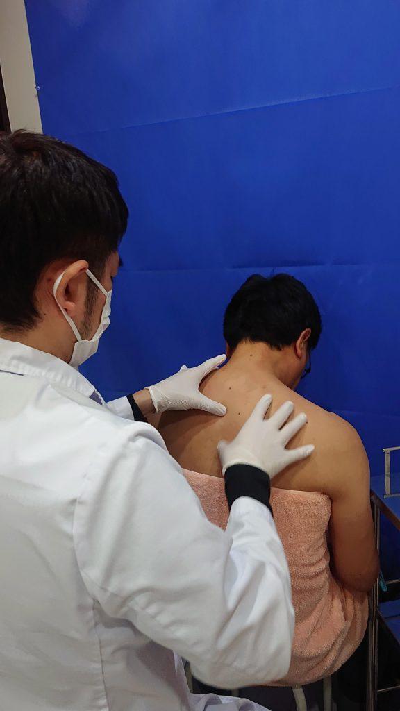 肩こり注射を打つツボを探している2枚目の画像です。左側にいる白衣を着た医師が右側の男性患者の背中をを左右の手の指先で押して探っています。