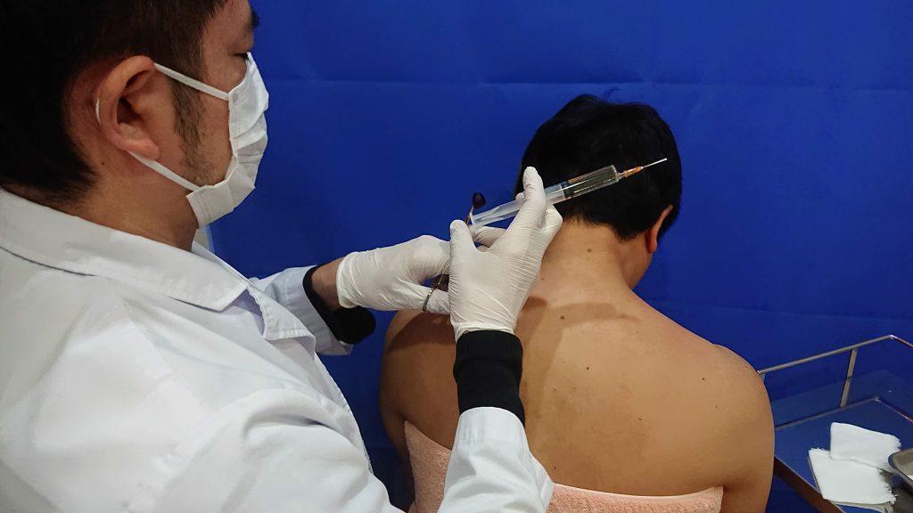 肩こり注射を始めるところの画像です。左側にいる医師が左手に消毒、右手に注射器を持っています。