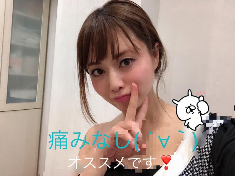 肩こり注射を受けた吉沢明歩さんの画像です。右肩がはだけていて、右手で左頬の前付近でピースサインをしています。